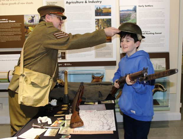 Photo of a young boy handling items in the exhibition. He is holding a rifle while an older man dressed in a soldiers uniform from World War One puts an armoured hat on his head.
