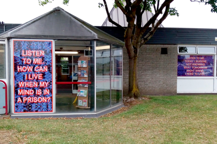 Photo of the outside of the library which has a piece of artwork in the window that says: Listen to me. How can I live when my mind is in a prison?