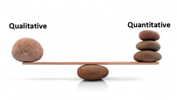 A photo of a see saw with pebbles on each end, illustrating the balance needed between quantitative and qualitative date