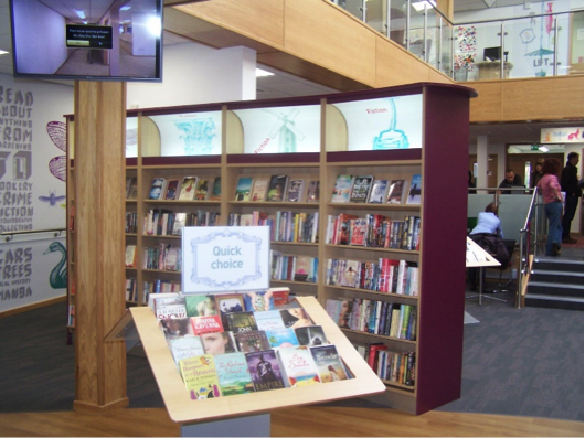Photo of inside Stapleford library showing a TV screen and different book cases.