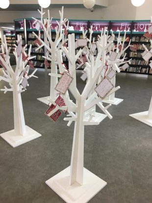 Photo of Redbridge Unsaid exhibition, consisting of a group of large model white trees with coloured labels tied on to them in place of leaves