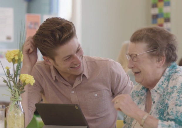 Photo of an elderly lady being shown how to use a computer by a young man