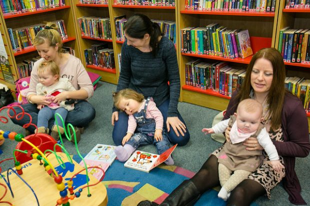 Photo of 3 women and their babies sitting on the floor of a library