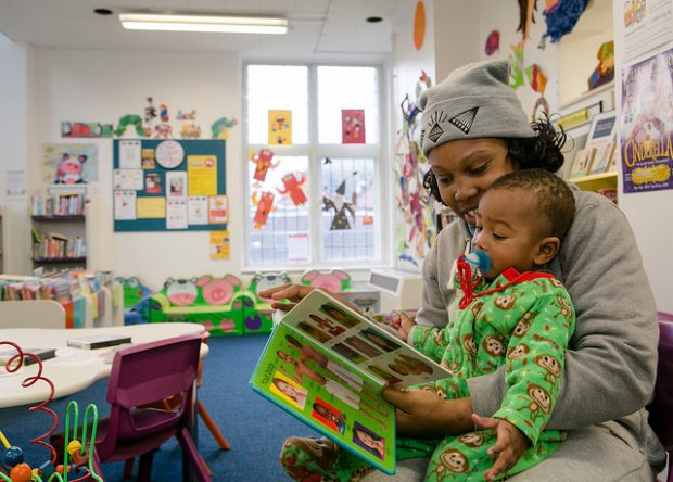 Photo of a mother reading with her child in a library