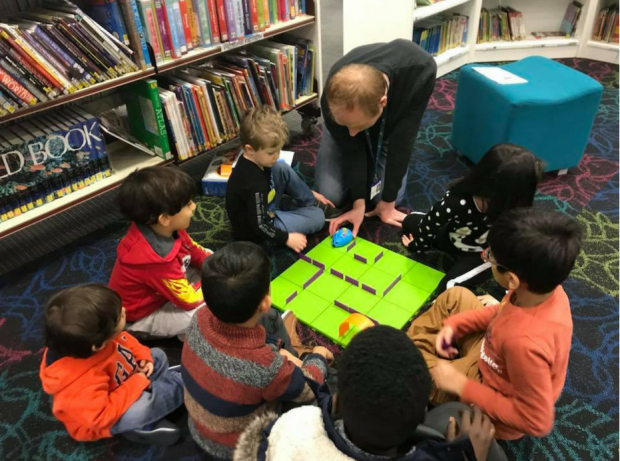 a group of young children sitting on the floor in a library, clustered around a board. an adult is sitting with them, showing them a robot about to enter a maze on the board