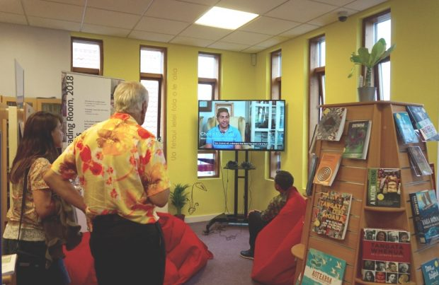 People in a corner of a library, watching a tv screen. the area is brightly coloured and some are sitting on beanbags