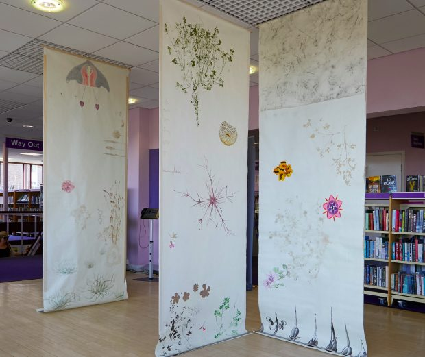 Photo of banners hanging from the library ceiling, showing plant and flower artwork