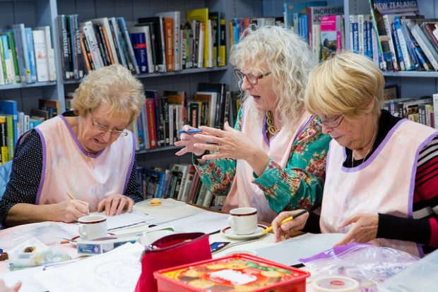 3 ladies round a table doing arts and crafts, in a library