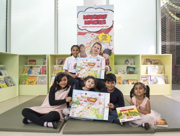 A group of children holding posters promoting the Summer Reading Challenge