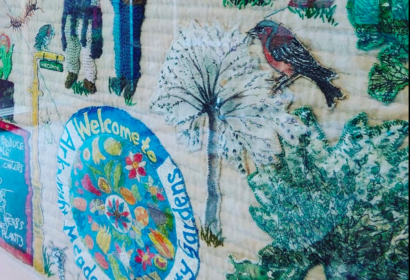 Photo of the detail of an embroidered wall hanging, showing a bird and a tree