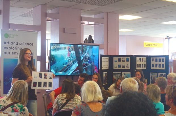 Photo of a woman giving a presentation in front of an audience in a library