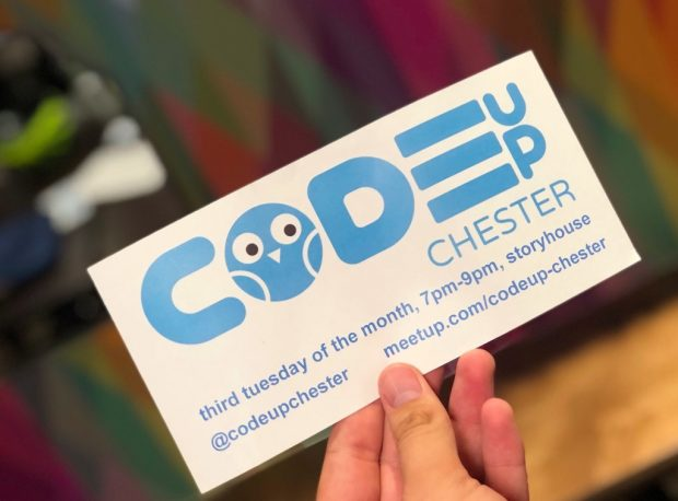 Hand holding a card promoting codeup Chester events - the letter o in the log is in the shape of an owl