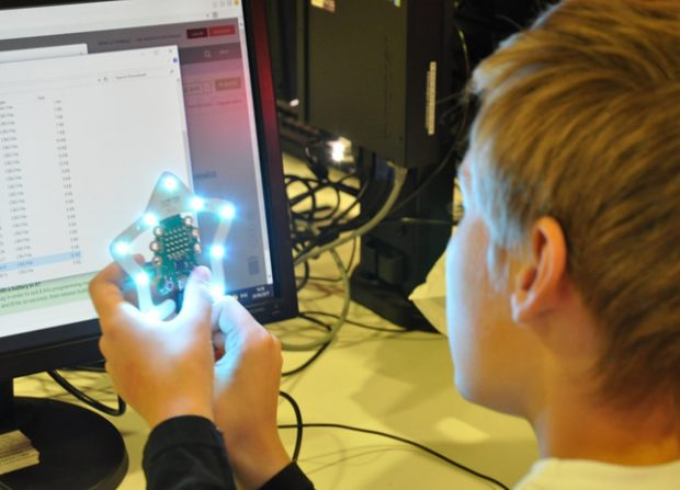 A young boy sitting in front of a computer screen, holding a micro:bit computer, wich is surrponded by bright lights in the shape of a star