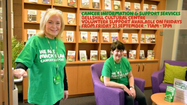 Two women wearing macmillan green t shirts in a library