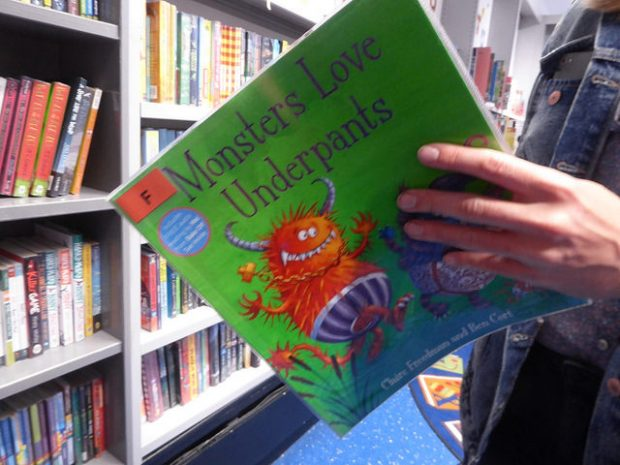 closeup of someone reading the child's picture book Monsters love underpants, in a library