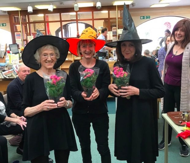 3 women in a library - dressed in black and wearing pointed witches hats