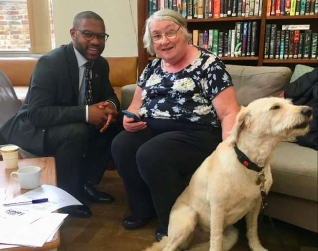Man and older woman sitting in a library, her guide dog at her feet
