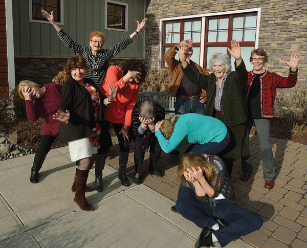 Photo of a group of women outside a stone building striking dramatic poses
