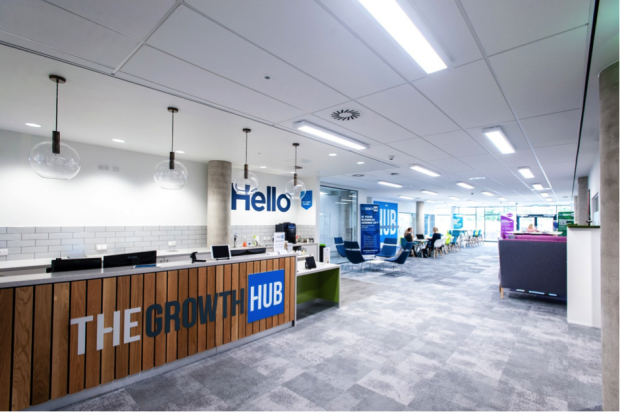 Large room with bright lights and desks, and a sign saying The Growth Hub