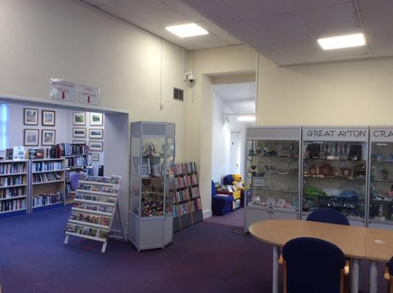A photo of inside Great Ayton Discovery Centre, showing bookcases, a table and chairs and display cases
