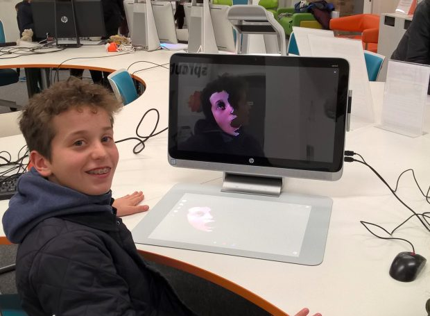 Young library visitor who has scanned his own face, using the HP Sprout.