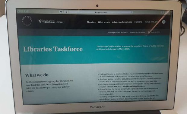 A photo of a laptop screen showing the Libraries Taskforce page on Arts Council England's website