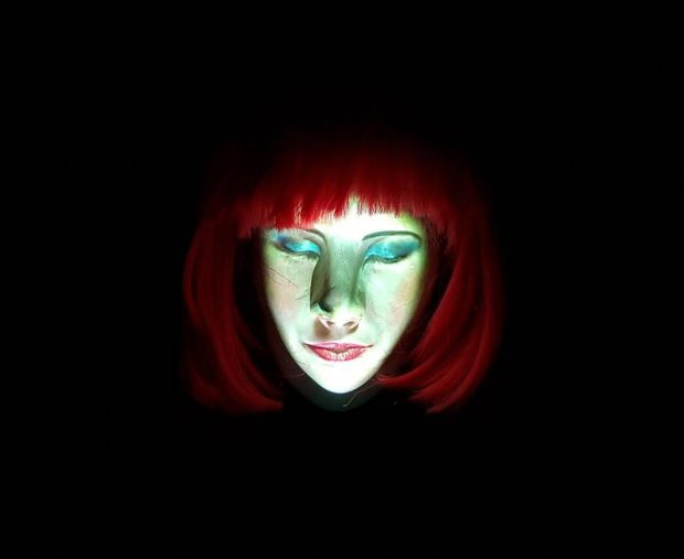 Photo of a red headed woman against a black background