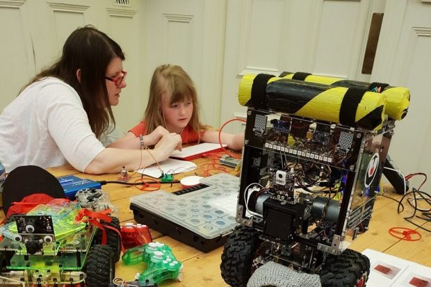 A photo of a woman and girl who are creating a circuit for a robot