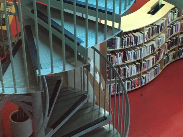 Photo of the inside of a library with a spiral staircase