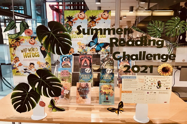 Twelve books on a clear tiered, table top, stand, behind a clear screen decorated with the words 'Summer Reading Challenge 2021', Summer Reading Challenge posters and stickers of flowers, large leaves, butterflies
