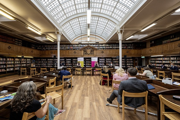 Battersea Library reading room, showing three sides of bookshelves, and gallery with second floor of bookshelves. The room has a curved glass roof, banks of wooden desks with wooden chairs. Eight audience members are sitting at the desks, looking towards the far end of the room, where Caroline Dinenage MP is speaking, flanked by two other presenters.