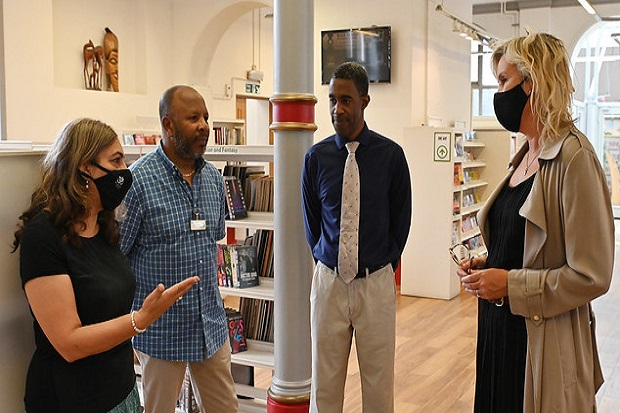 Three members of Battersea library staff (standing to the left and in the centre of the image) speaking with Caroline Dinenage MP (to the right of the image). Group is standing in front of the library bookshelves